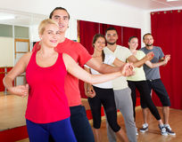 Smiling young adults dancing salsa stock photography