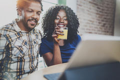 Smiling young african american couple having online conversation together via touch tablet at the morning in living room Royalty Free Stock Photography