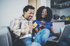 Smiling young african american couple shopping online through modern laptop using credit card at home. Horizontal Royalty Free Stock Image