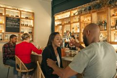 Smiling African American couple enjoying drinks together in a bar. Smiling young African American couple talking over drinks while out together on a date in a stock images