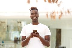 Smiling young african american man with mobile phone standing outside in city. Portrait of smiling young african american man with mobile phone standing outside Royalty Free Stock Image