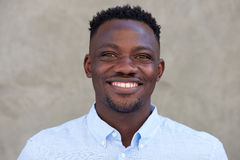 Smiling young african american man standing against a wall Royalty Free Stock Image