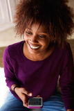 Smiling young african american woman with cell phone Stock Photos
