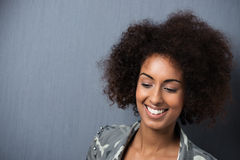 Smiling young African American woman. With downcast eyes and a wild afro hairstyle against a dark grey background with copyspace Royalty Free Stock Image