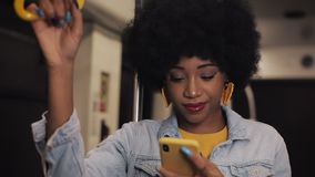 Smiling young african american woman holds the handrail and using smartphone at public transport. Night time. Rain and stock video footage
