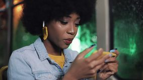 Smiling young african american woman holds the handrail and watching video on the smartphone at public transport. Night stock footage