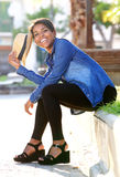 Smiling young african american woman sitting outside Stock Image