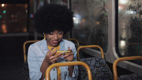Smiling young african american woman watching funny video on the smartphone riding in the public transport. Night time stock video footage