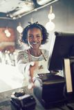 Smiling young African entrepreneur extending a handshake in her. Smiling young African cafe owner standing at a point of sale terminal in her bistro extending a royalty free stock photos