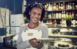 Smiling young African cafe owner using a digital tablet. Young African entrepreneur in an apron smiling and using a digital tablet while standing in front of the royalty free stock photo