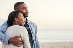 Smiling young African couple enjoying a sunset at the beach. Romantic young African couple enjoying a late afternoon together on a sandy beach at sunset while stock images