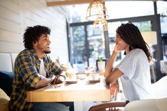 Smiling young african couple sitting at a table at a cafe drinking coffee and talking together. While out on a date royalty free stock photos