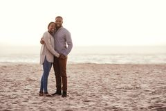 Smiling young African couple standing on a beach at sunset stock photography