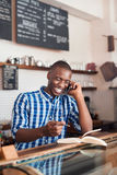 Smiling young African entrepreneur hard at work in his cafe Stock Images