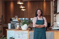 Smiling young African entrepreneur standing in her cafe royalty free stock images