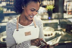 Smiling African entrepreneur using a tablet in her trendy cafe. Smiling young African entrepreneur wearing an apron and using a digital tablet while standing in royalty free stock photography