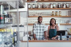 Smiling young African entrepreneurs standing at their bakery counter. Portrait of two successful young African entrepreneurs standing together behind the counter royalty free stock images