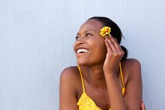 Smiling young african lady holding a flower. Close up portrait of smiling young african lady holding a flower and looking away stock image