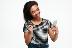 Smiling young african lady using phone and holding debit card. Royalty Free Stock Image
