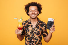 Smiling young african man drinking cocktail and holding tickets. Stock Images