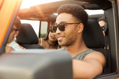 Smiling young african man driving a car. And having fun with his friends Stock Photo