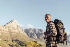 Smiling young African man enjoying the view while out hiking. Smiling young African man wearing a backpack standing on a trail looking at the view while hiking Stock Photos