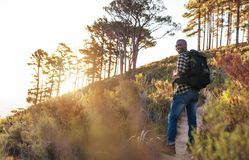 Smiling young African man hiking alone up a trail. Smiling young African man wearing a backpack walking up a trail while hiking alone in the hills on a sunny day royalty free stock photos