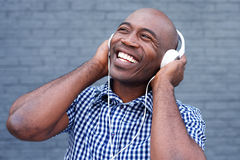 Smiling young african man listening to music Stock Photos