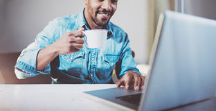 Smiling young African man making video conversation via modern laptop with friends while drinking black coffee in Royalty Free Stock Image