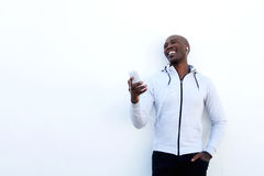 Smiling young african man with mobile phone and headphones. Portrait of smiling young african man with mobile phone and headphones standing against while wall Stock Photography