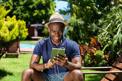 Smiling young african man sitting outdoors using digital tablet Stock Photography