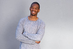 Smiling young african man standing against gray wall with arms crossed Stock Photography