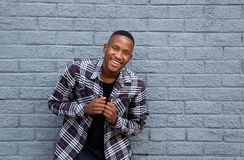 Smiling young african man standing against a gray wall. Portrait of a smiling young african man standing against a gray wall Royalty Free Stock Photos