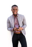 Smiling young african man standing with a mobile phone. Portrait of a smiling young african man standing with a mobile phone Stock Photo