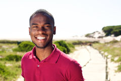 Smiling young african man standing outdoors Stock Photo