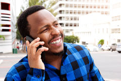 Smiling young african man talking on cellphone in the city Royalty Free Stock Images