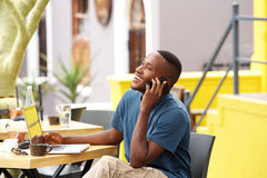 Smiling young african man talking on mobile phone at a cafe Stock Photos