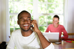 Smiling young african man talking on mobile phone at home Royalty Free Stock Photos