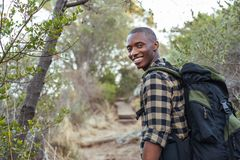 Smiling young African man hiking in the hills Royalty Free Stock Photography