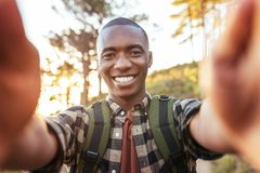 Smiling young African man taking selfies while hiking alone outdoors. Smiling young African man wearing a backpack taking a selfie while walking up a trail in stock images