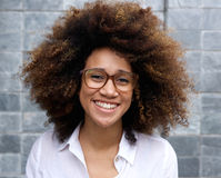 Smiling young african woman with afro and glasses. Portrait of smiling young african woman with afro and glasses Royalty Free Stock Photography
