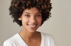 Smiling young African woman with an afro and natural complexion. Closeup portrait of a smiling young African woman with an afro and natural complexion standing royalty free stock photo