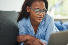 Smiling African woman relaxing on her sofa using a laptop. Smiling young African woman browsing online with a digital tablet while lying on the sofa in her royalty free stock photography