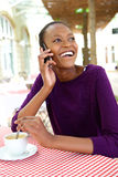 Smiling young african woman at cafe making phone call Stock Photos