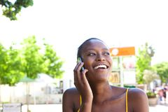 Smiling young african woman in the city talking on cellphone Stock Photography