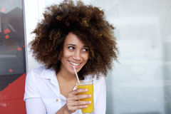 Smiling young african woman drinking juice at outdoor cafe. Portrait of a smiling african american woman drinking juice Stock Photos