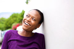 Smiling young african woman leaning against wall Stock Photo