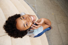 Smiling young african woman looking up and using mobile phone Stock Photography