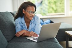 Young African woman lying on her sofa using a laptop royalty free stock photography