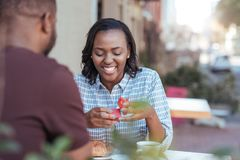 Smiling young African woman opening a gift from her boyfriend. Excited young African women opening a wrapped present from her boyfriend while sitting together at Stock Photo